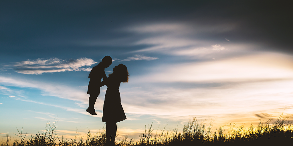 silhouette-of-mother-playing-with-her-son-in-the-meadow